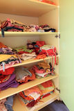 Wardrobe with child clothes on shelves royalty free stock image