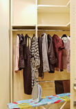 Wardrobe with clothes and ironing board stock image