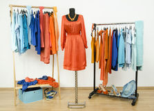 Wardrobe with complementary colors orange and blue clothes arran Stock Photos