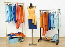 Wardrobe with complementary colors orange and blue clothes arranged on hangers. Stock Image
