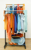 Wardrobe with complementary colors orange and blue clothes. Stock Image