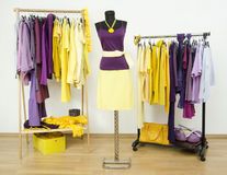 Wardrobe with complementary colors purple and yellow clothes arranged on hangers. Dressing closet with violet and yellow clothes and accessories and an outfit royalty free stock photos