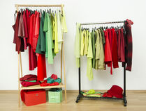 Wardrobe with complementary colors red and green clothes arranged on hangers. Stock Photo