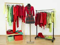 Wardrobe with complementary colors red and green clothes arranged on hangers. Stock Image