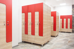 Wardrobe in the gym. Red wooden sports wardrobe in the gym for clothes Royalty Free Stock Photos