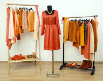 Wardrobe with orange clothes arranged on hangers and a dress on a mannequin. Royalty Free Stock Photo