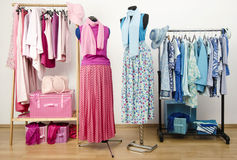 Wardrobe with pink and blue clothes with outfit on two mannequins. Royalty Free Stock Images