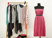 Wardrobe with polka dots clothes arranged on hangers and a pink dress on a mannequin. Royalty Free Stock Photography