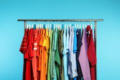 Wardrobe rack with different bright clothes. On color background stock photo