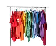 Wardrobe rack with different colorful clothes on white. Background stock photography