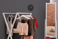 Wardrobe rack with women`s clothes. In dressing room stock photography
