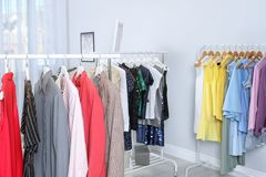 Wardrobe racks with different stylish clothes. In light room royalty free stock images