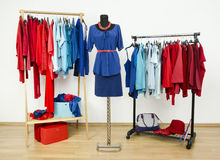 Wardrobe with red and blue clothes arranged on hangers. Royalty Free Stock Photos