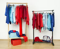 Wardrobe with red and blue clothes hanging on a rack nicely arranged. Royalty Free Stock Photography