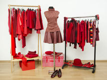 Wardrobe with red clothes arranged on hangers and an outfit on a mannequin. Royalty Free Stock Photography