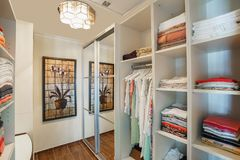 Wardrobe room in a private villa. Open cupboards with clothes folded in them stock images
