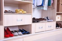 Wardrobe shelves with different shoes. Wardrobe shelves with different stylish shoes royalty free stock images