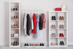 Wardrobe shelves with different stylish shoes and clothes indoors. Idea for interior design stock image