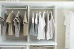 Wardrobe with shirts and pants hanging Stock Image