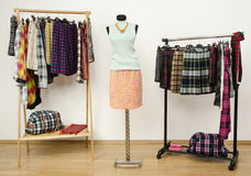 Wardrobe with tartan clothes arranged on hangers and an outfit on a mannequin. Stock Photography