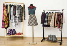 Wardrobe with tartan clothes arranged on hangers and an outfit on a mannequin. Stock Photos