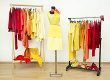 Wardrobe with yellow, orange and red clothes arranged on hangers. Stock Images