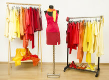 Wardrobe with yellow, orange and red clothes arranged on hangers and a red outfit on a mannequin. Stock Images