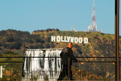 Wardrobes for the Stars. A mover rolls a rack of costumes in front of the Hollywood sign Stock Images