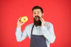 Ware feiten over suiker Geen manier Verglaasde doughnut van de Hipster de gebaarde bakker greep op rode achtergrond Koffie en bak stock foto's