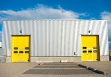 Warehouse. Industrial warehouse with two identical yellow roller doors Stock Photography