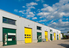Warehouse. Industrial warehouse with green and yellow roller doors Stock Photography