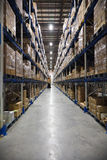 Warehouse aisle. A warehouse aisle with a forklift truck in the background royalty free stock image