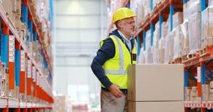 Warehouse arbetaren som lidande från tillbaka smärtar, medan arbeta arkivfilmer