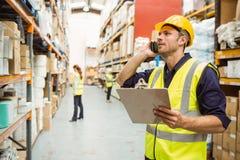 Warehouse arbetaren som talar på den hållande skrivplattan för telefonen Arkivbild