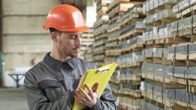 Warehouse arbetarhandstil på hans skrivplattaanseende på lagringen arkivfilmer