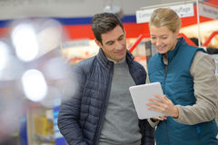 Warehouse assistant checking for customer product in tablet Stock Photography