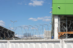 Warehouse behind the fence with barbed wire. stock photos