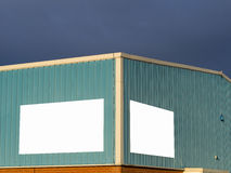 Warehouse with blank signs for message against stormy cloud background Stock Photo