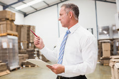 Warehouse boss checking his inventor Stock Photography