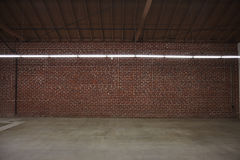 Warehouse with brick wall. A large warehouse with cement floor and brick walls and long flourescent track lights royalty free stock image