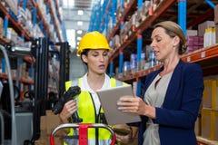 Warehouse chefen med den påverkande varandra kvinnliga arbetaren över den digitala minnestavlan Arkivbild