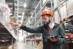 Warehouse chefen som kontrollerar hans inventarium i ett stort lager Arkivfoto