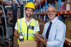 Warehouse chefen som rymmer den digitala minnestavlan medan den manliga arbetarscanningbarcoden royaltyfri bild