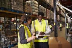 Warehouse chefen som talar med kvinnan som använder barcodeavläsaren arkivbild