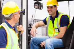 Warehouse co-workers chatting. Warehouse co-worker chatting during break on forklift royalty free stock photo