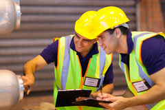 Warehouse co-workers machinery. Warehouse co-workers in safety gear inspecting machinery Stock Images