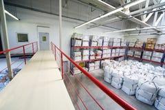 Warehouse con el montón de sacos blancos grandes en piso y estantes Imágenes de archivo libres de regalías