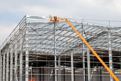 Warehouse construction. Construction of a new warehouse with construction worker on a crane royalty free stock images