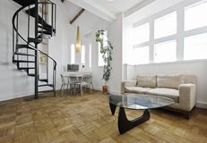 Warehouse conversion apartment. With metal spiral staircase royalty free stock photos