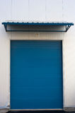 Warehouse door. Blue closed roller warehouse door with sun shield Royalty Free Stock Images